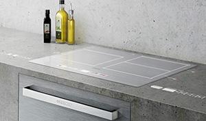 Technologie Grundig VUX : projection d'informations et de boutons de commande sur une table de cuisson et un plan de travail à partir d'une hotte